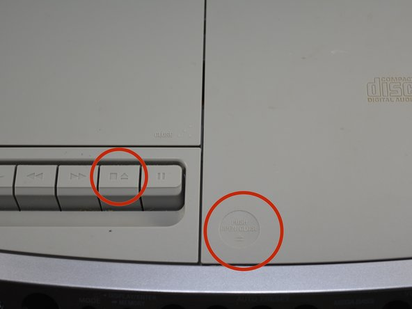 To open the CD door push on the bottom left corner of the CD door. To open the cassette door push the button that is to the left of the pause button.
