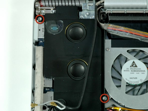 Remove the two silver T6 Torx screws from the top left 8 mm and bottom right 10 mm corners of the left speaker assembly.