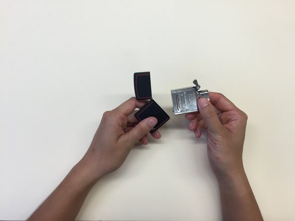 Open the lid of the Zippo and extract the insert – firmly grip either side of the flint wheel with 2 fingers. Hold the bottom of the Zippo lighter with your other hand and pull up on the metal to free the insert of the lighter from its case.