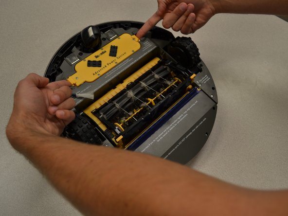 Identify the yellow plastic rectangular battery, directly to the right of the spinning brush.