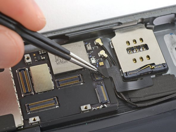 Use tweezers to peel and remove the piece of tape covering the SIM board cable connector on the logic board.