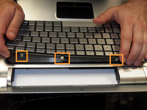 Flip the laptop over and open it so the keyboard is visible.