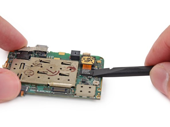 Use the flat end of a spudger to disconnect the rear-facing camera cable connector from its socket on the motherboard.