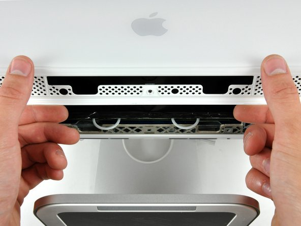 While holding the RAM arms in with your thumbs, lift the lower edge of the front bezel enough to clear the rear case.