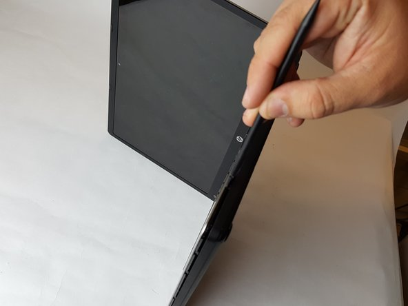 Slide the spudger with a twisting motion along the entire perimeter of the laptop until the top cover is separated from the frame of the device.