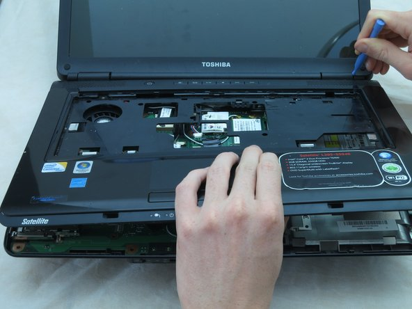 Use a plastic opening tool to pry the laptop's upper casing off of its lower casing. Move the opening tool around the sides of the case to help separate them.