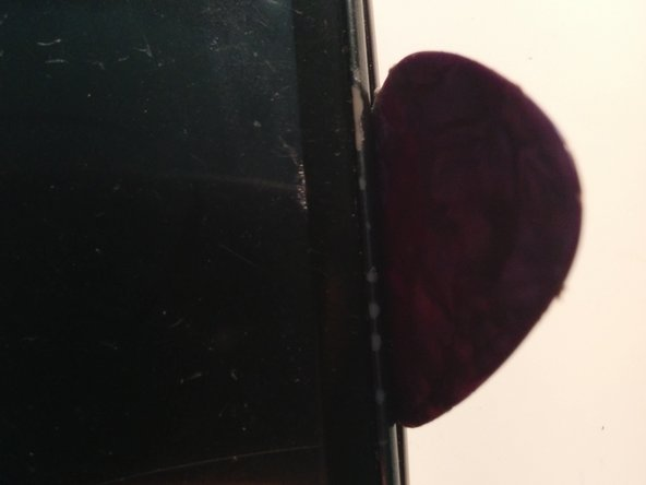 Slide a guitar pick between the sliver bezel and the rear of the phone