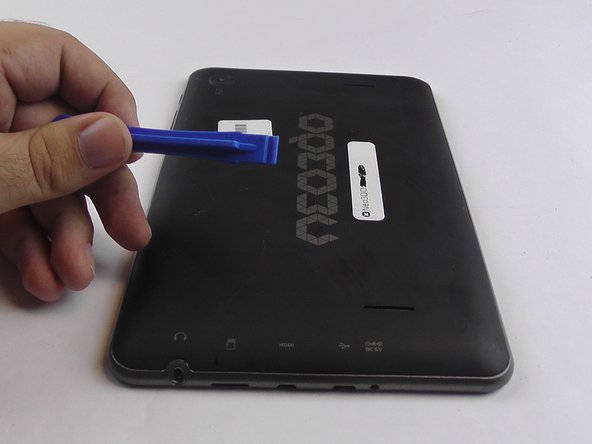 Insert the plastic opening tool between the metal frame and the plastic back panel, as shown.