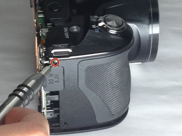 Remove the 3.0mm Phillips #000 screw located above the grey power flap on the side of the camera.
