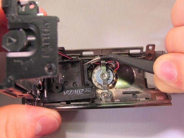 Pull on the black piece that is connected to the under part of the zoom lever using the tweezers while you push the back piece into an angle. BE CAREFUL not to disconnect the red and black wires (The zoom lever is ready to be replaced.)