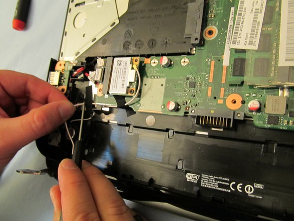 Image 1/2: Remove the wifi cable by unfastening it from the wifi card first, then following the wire. Remove any tape necessary.