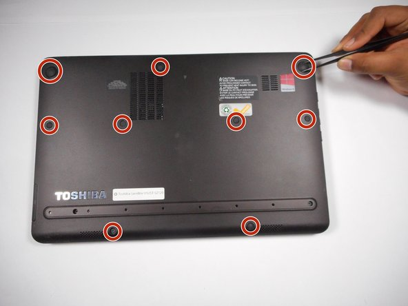 Use tweezers to remove the 9 rubber grip pads on the back panel of the laptop.