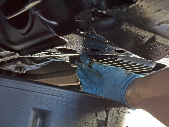 Make sure the oil drain pan is still in position under the oil drain plug.