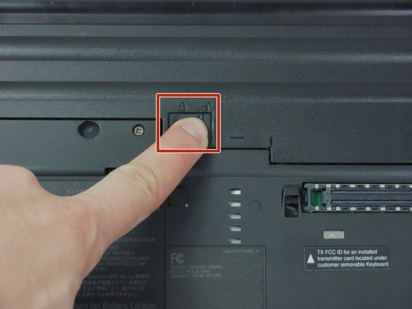 Turn the computer over to see the small tab on the battery located near the top of the Thinkpad.