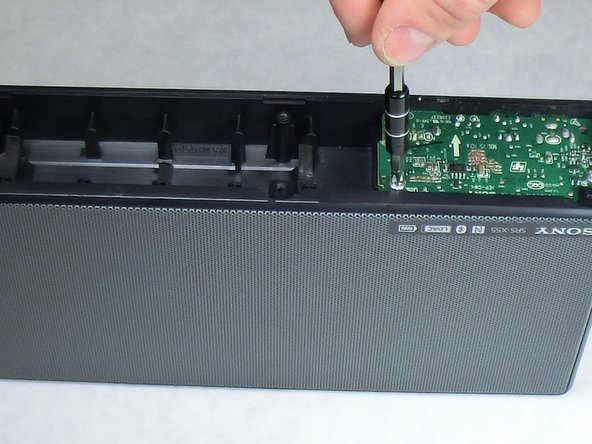 Locate the two 3.5 mm screws on the bottom of the I/O board and remove them using a Phillips head #2 screwdriver.