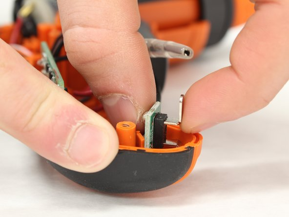 Locate the battery contact board near the bottom/rear side of the screwdriver.