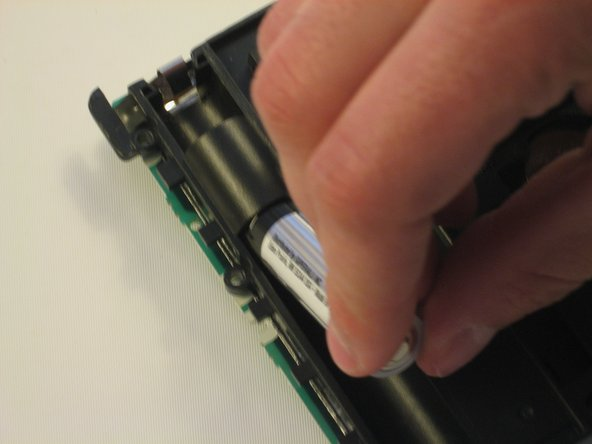 Remove the bottom batteries by pressing the battery towards you while pulling it out from the far end.