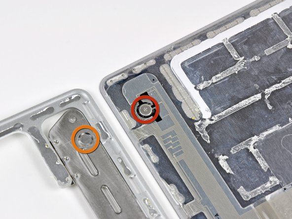 "Image 2/2: The Magic Trackpad has a unique way of triggering the mouse button. As you press down on the top surface of the Trackpad, the two rubber feet near its front edge push up on the hinged plate and set screw (shown in orange) attached to the chassis. This squeezes the electronic mouse button switch (shown in red), producing the characteristic ""click""."