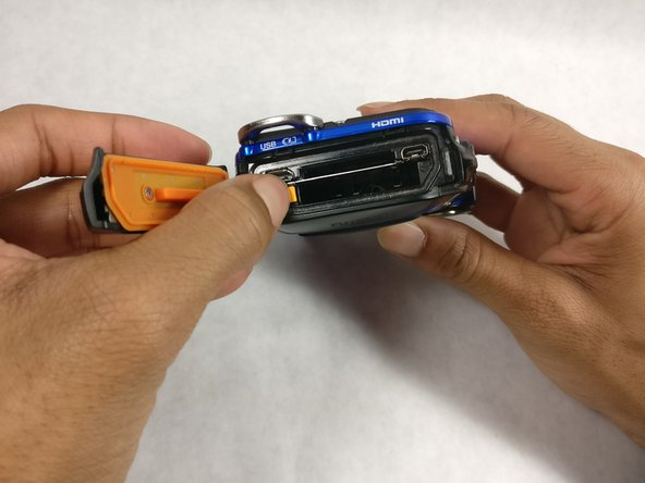 Pull the orange tab towards the hinge to release the battery.