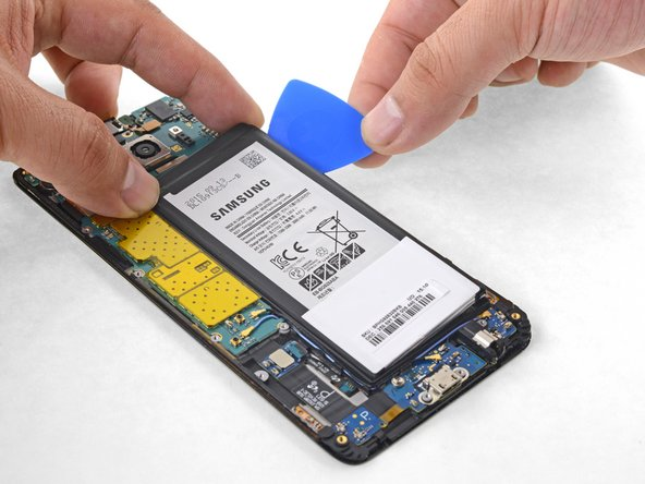 Twist the opening pick to lift the battery away from the display frame.