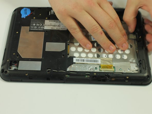 Start to gently pry the back of the device off, while leaving it loosely in place.