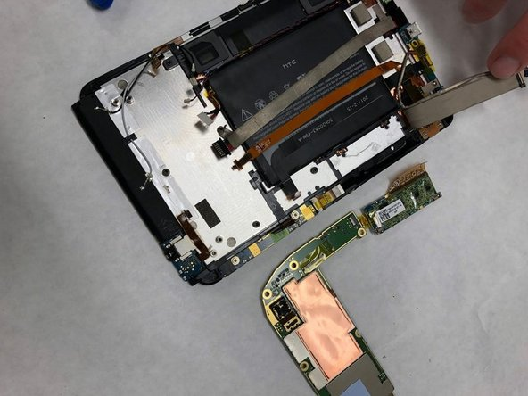 Remove the motherboard. Note that the flex screen will not be removed with it and will remain attached to the tablet frame.