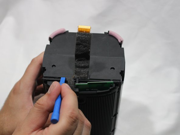 Using a plastic opening tool, separate the motherboard from the speaker.