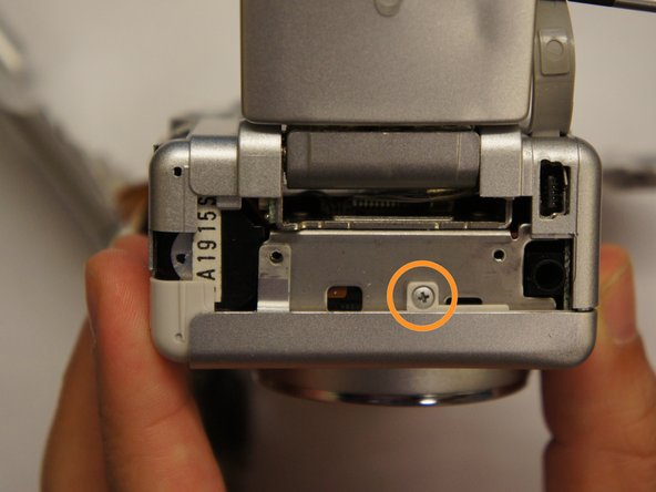 Remove indicated screw holding front of camera in place.