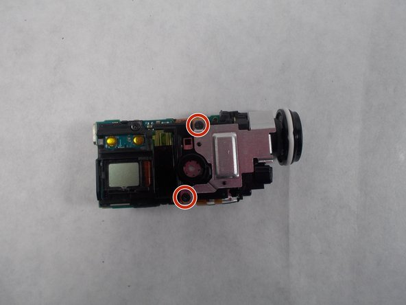 Now, grab the lens and pull the body out of the plastic, this will reveal the insides of the device. You'll see a screw on the top of the device, towards the front, remove this screw. Next pull the tabs on the bottom and top of the lens, and pull outward, this will remove the lens housing from the body.