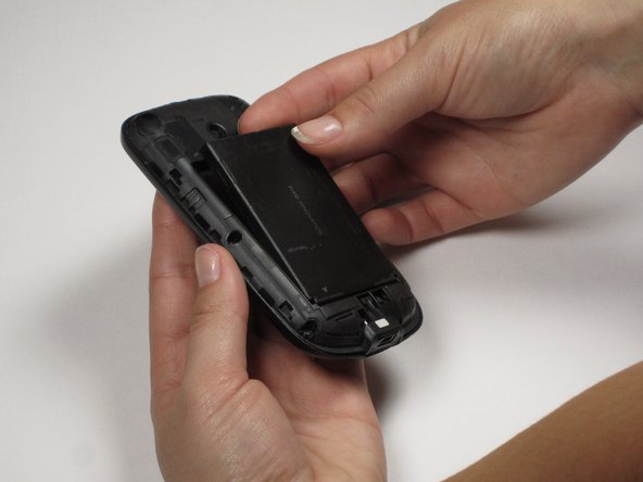 Insert thumb and pointer finger into the notch above the battery. Pull the battery away from the rest of the phone and set aside.