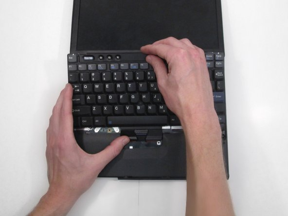 Push firmly upward with both thumbs. This will detach keyboard from base.