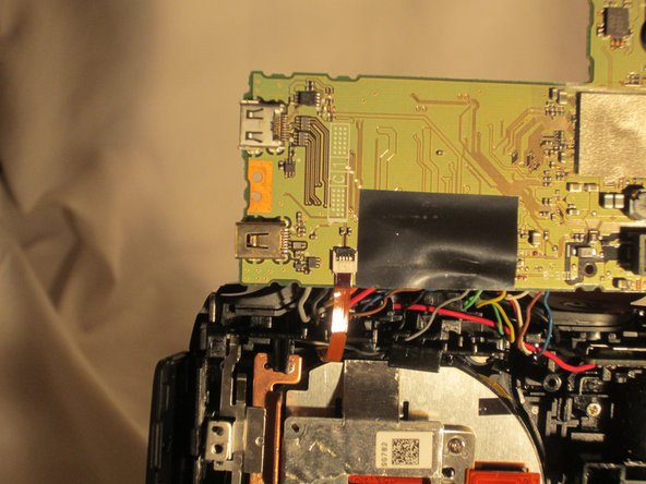 Once the flex circuits are removed, the motherboard can be lifted and the device can be accessed for replacement.