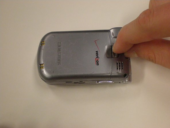 Remove the battery by pinching and unlatching the clip located above the Verizon logo on the back of the phone.