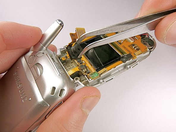 Using tweezers, remove the camera from the cellphone casing.