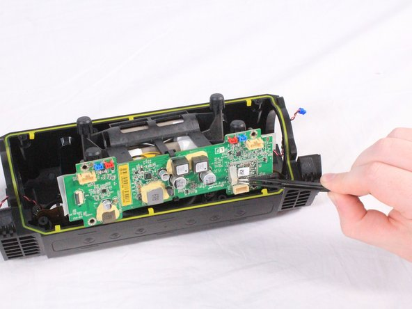 The motherboard is connected to the battery directly. Carefully lift the battery and motherboard unit halfway out of the casing.