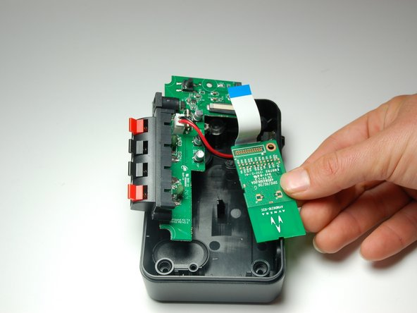 Using your fingers, pull the ribbon wire out from the black retaining flap in order to completely disconnect the wireless audio module chip.