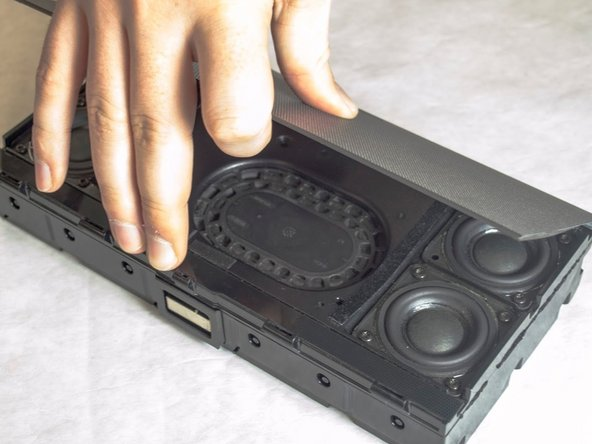 Pull the metal grill off of the speaker.