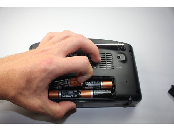 "Image 1/3: The battery's positive terminal is indicated by a ""+"" on the side."
