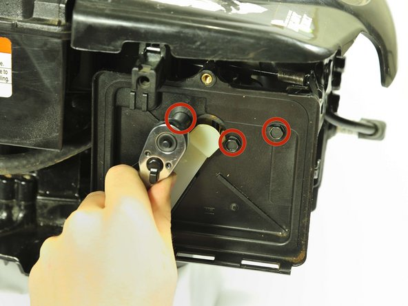 "Use a socket wrench with a 5/16"" hex bit to remove three 20mm bolts behind the air filter."