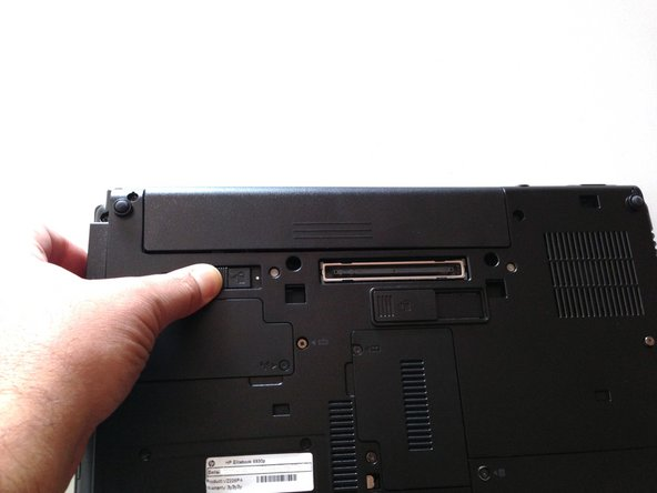 Image 2/3: Push release button to the left to release battery and gently pull battery from the laptop