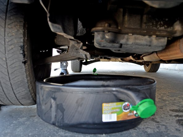 Reposition the oil drain pan so that it catches the oil that will spill when you remove the oil filter.