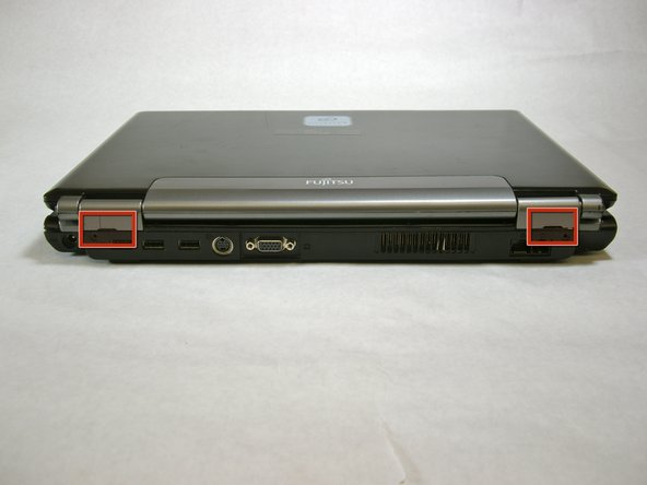 Use a spudger to lift the back of the hinge cover on the left and right sides of the computer.