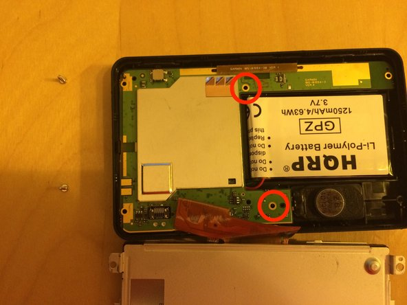 Image 2/2: Using your T5 driver, remove the two screws that hold the circuit board in place.