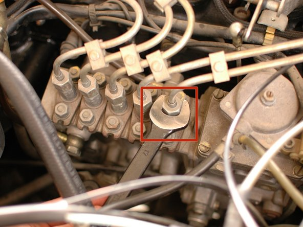 Now, use a 17mm wrench loosen the rear-most nuts on the hard lines at the injection pump.