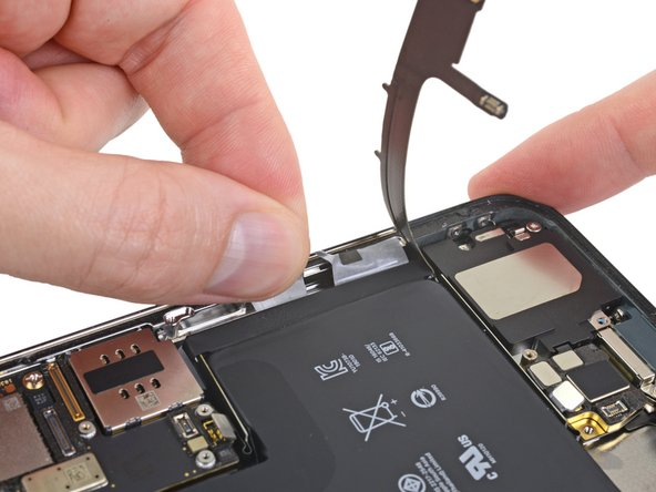Using the same procedure as before, pull both tabs at the same time to stretch and remove the remaining adhesive strip holding the battery in place. Try not to snag the adhesive on the edge of the iPhone.
