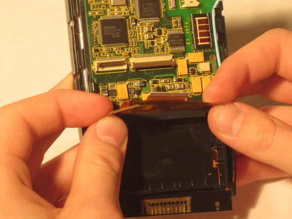 Located near the bottom of the motherboard will be two ZIF connector tabs. Gently lift up the flap that secures these tabs and remove the tabs.