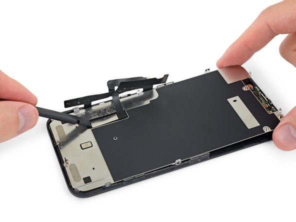 Grab the LCD shield by its top edge and swing it upward a few degrees.