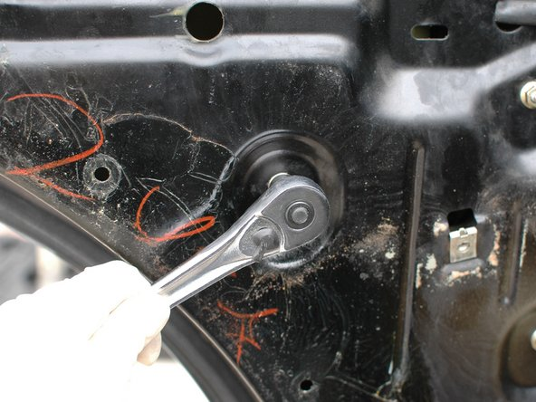 Loosen and remove the 10mm bolt that holds the final connection point of the regulator to the door shell.
