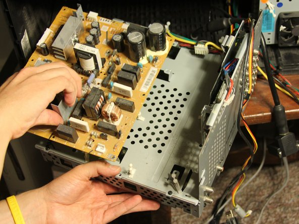 Remove the power supply board from its protective case by pulling it straight up and away from the case.