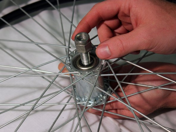 Image 1/3: Insert the bolt into the axle so that the wheel is attached to the side of the frame